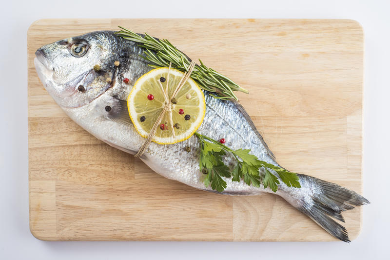 Gilt-head sea bream with spices and herbs. Raw gilt-head sea bream with spices and herbs on a cutting board ready to be cooked stock photo