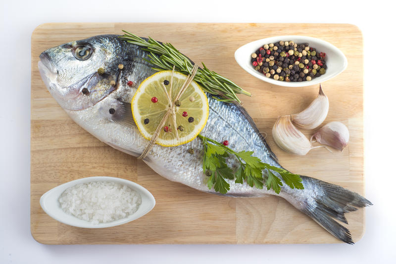 Gilt-head sea bream with spices and herbs. Raw gilt-head sea bream with spices and herbs on a cutting board ready to be cooked stock photography