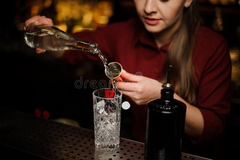 Gim de derramamento do barman fêmea em um vidro de cocktail imagem de stock
