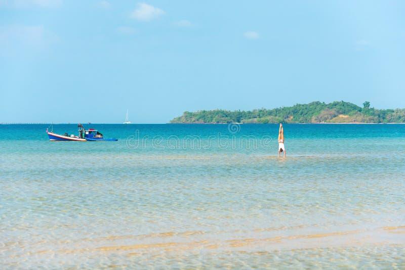 Gimnasia por el mar, un retrato del ejercicio de formaci?n atractivo del gimnasta de la chica joven en el mar azul en soleado fotos de archivo libres de regalías