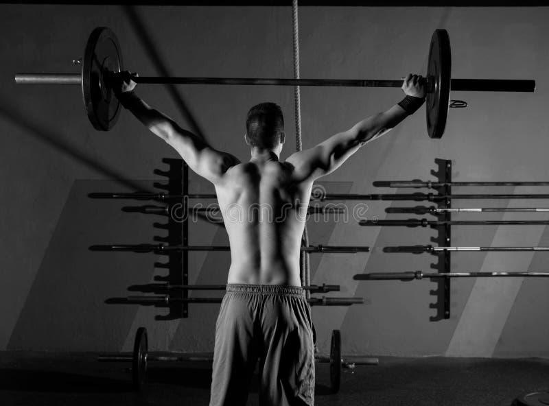 Gimnasio del entrenamiento de la vista posterior del hombre del levantamiento de pesas del Barbell fotografía de archivo libre de regalías