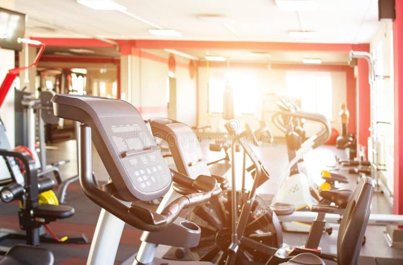 Gimnasio interior con el nuevos equipo de deportes, ruedas de ardilla y salud, sol, fondo, pista del funcionamiento, cardiia foto de archivo libre de regalías