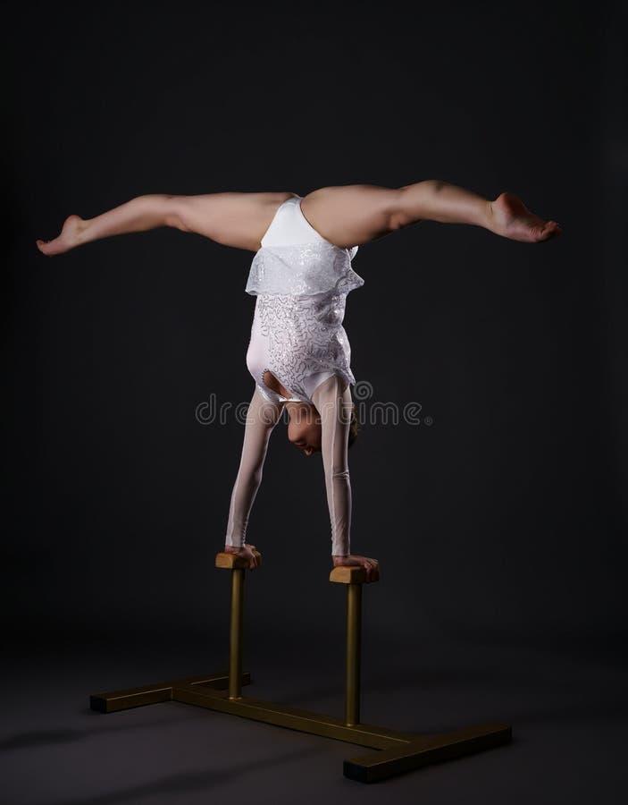 Gimnasta encantador que hace posición del pino en soportes del circo imagenes de archivo