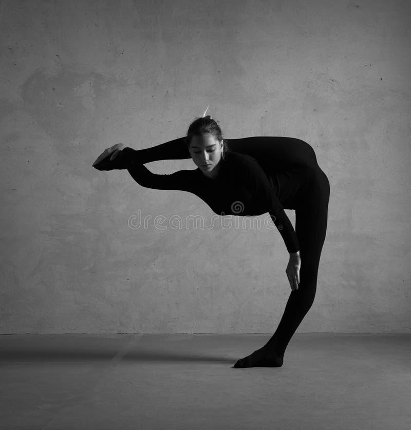 Gimnasta flexible que presenta en ropa negra imágenes de archivo libres de regalías