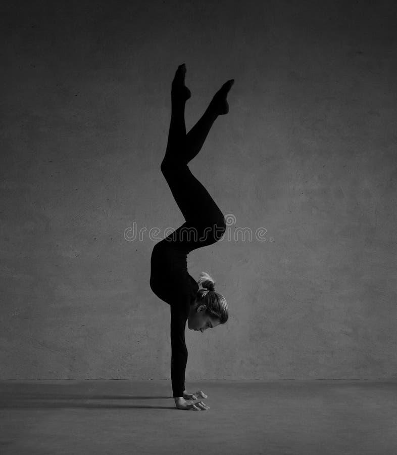 Gimnasta flexible que presenta en ropa negra fotografía de archivo libre de regalías