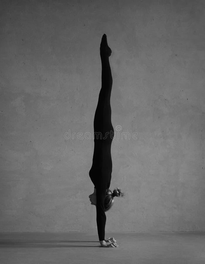 Gimnasta flexible que presenta en ropa negra fotografía de archivo