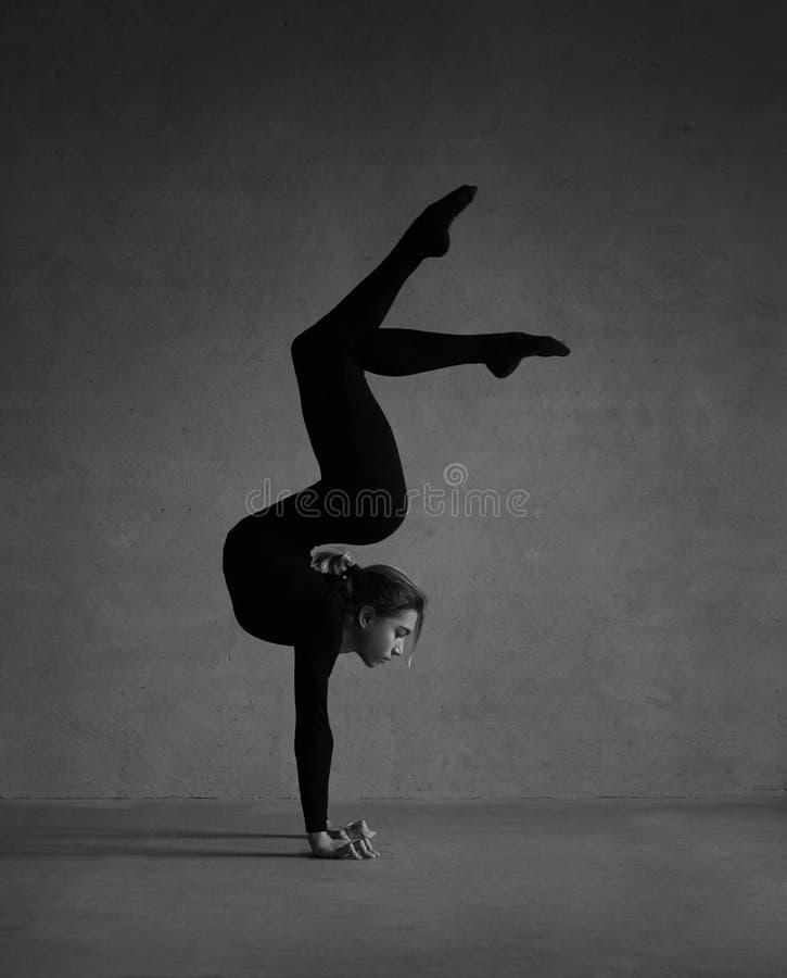 Gimnasta flexible que presenta en ropa negra fotos de archivo