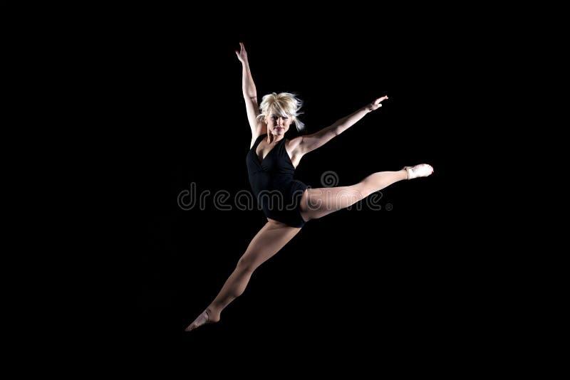 Gimnasta hermoso de la mujer joven que salta en el aire imagenes de archivo