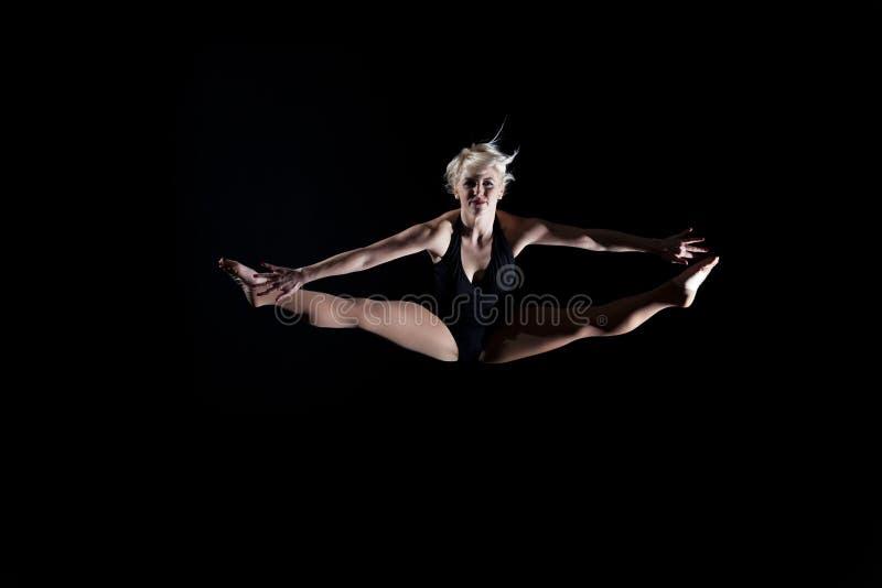 Gimnasta hermoso de la mujer joven que salta fracturas imagen de archivo