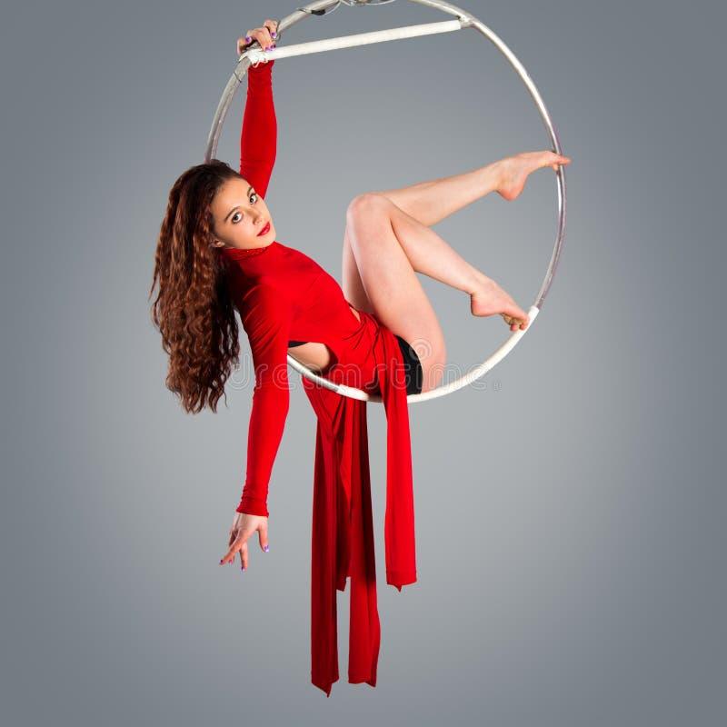 Gimnasta hermoso plástico de la muchacha en el anillo acrobático del circo en traje color carne foto de archivo libre de regalías