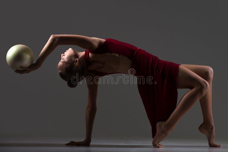 Gimnastyczki dziewczyna robi bridżowemu ćwiczeniu z piłką obraz royalty free