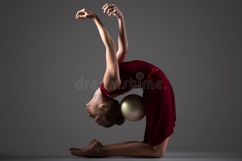 Gimnastyczki dziewczyna zgina backwards z piłką zdjęcie stock