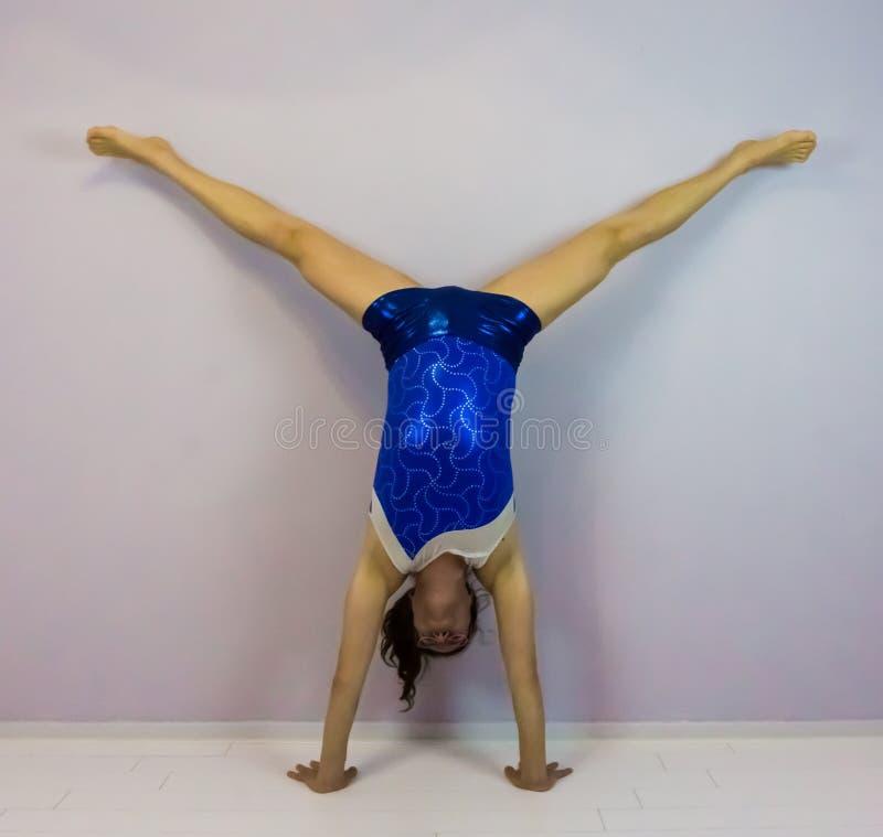 Ginástica acrobática um pino rachado médio pré-formado por uma menina nova do transgender que veste uma malha brilhante azul imagem de stock