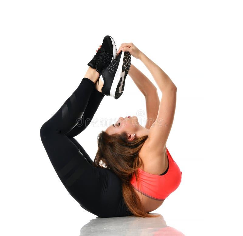 Ginástica de mulher nova do esporte que faz esticando o exercício da aptidão no gym do esporte imagens de stock