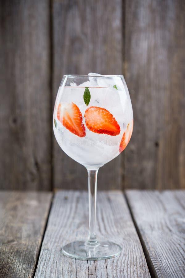 Gin con la fragola ed il ghiaccio in vetro di vino fotografie stock