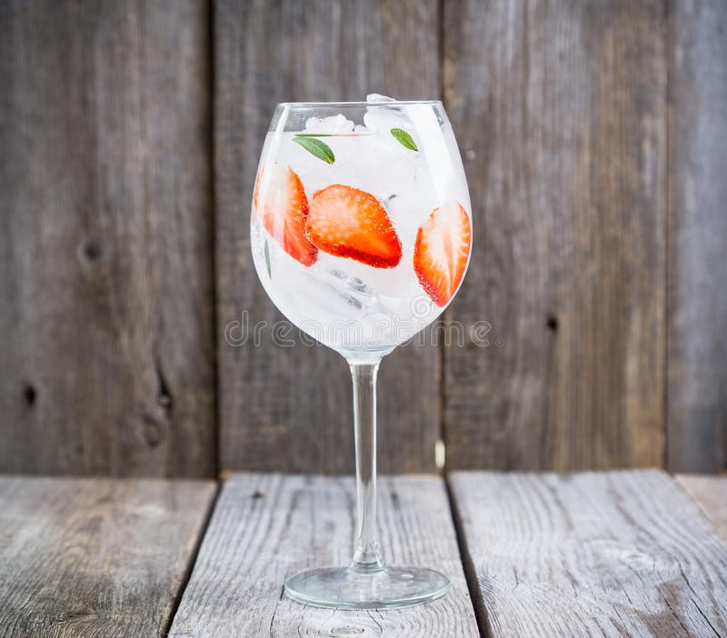Gin con la fragola ed il ghiaccio in vetro di vino immagine stock libera da diritti