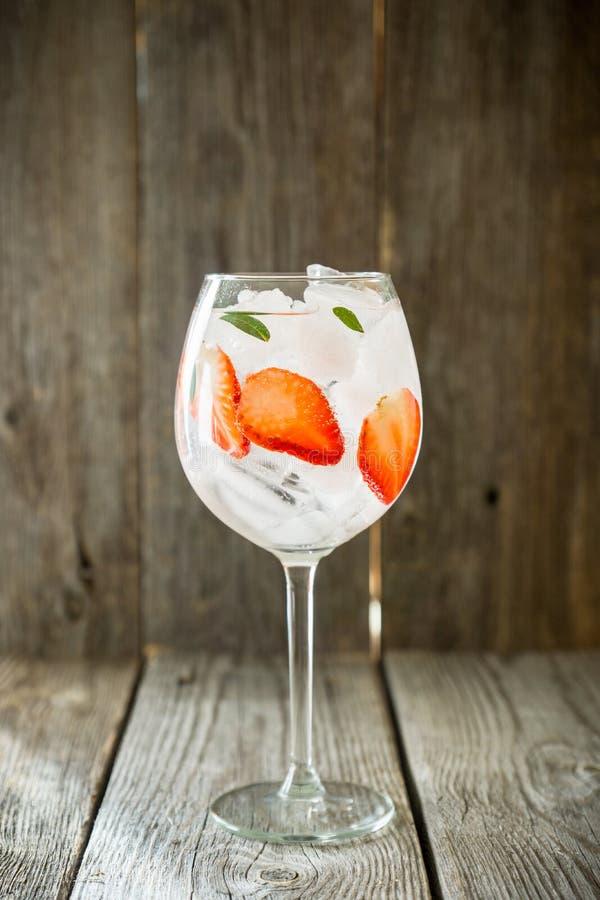 Gin con la fragola ed il ghiaccio in vetro di vino fotografia stock libera da diritti