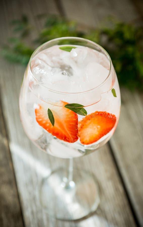 Gin con la fragola ed il ghiaccio in vetro di vino fotografie stock libere da diritti