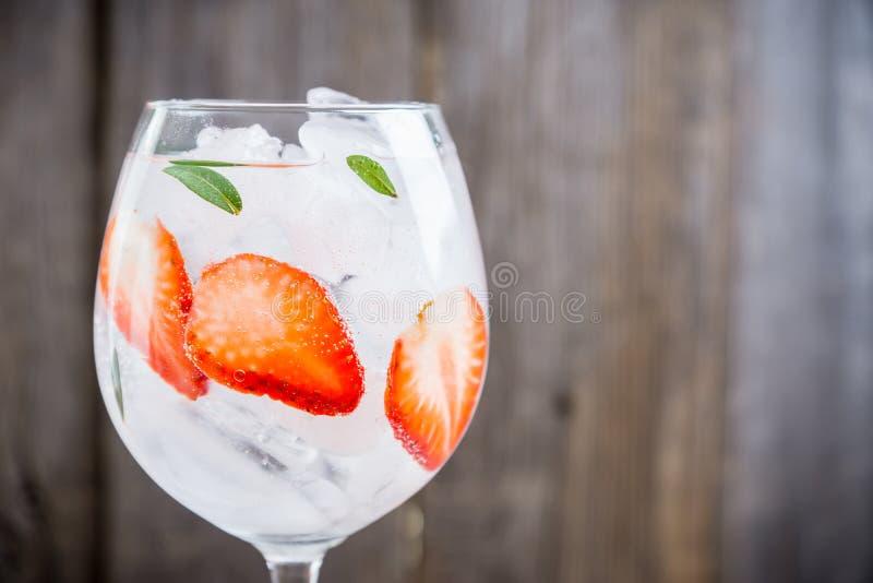 Gin con la fragola ed il ghiaccio in vetro di vino fotografia stock