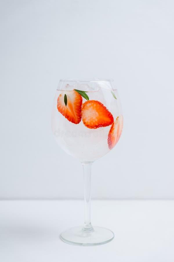 Gin con la fragola ed il ghiaccio in vetro di vino immagine stock