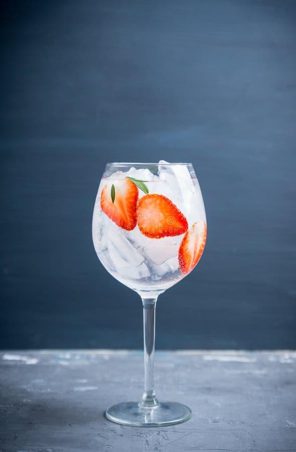 Gin con la fragola ed il ghiaccio in vetro di vino immagini stock libere da diritti