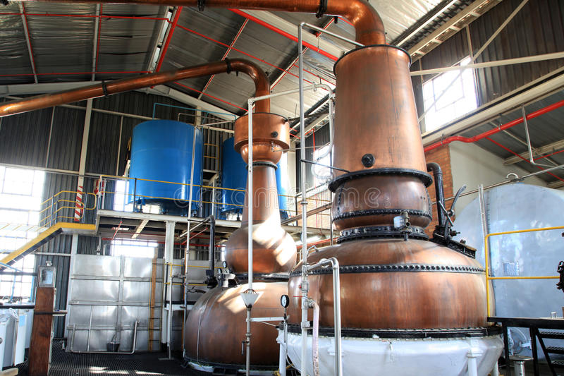 Gin kettles. Old brass gin kettles in a distill. Production of gin through distill process royalty free stock image