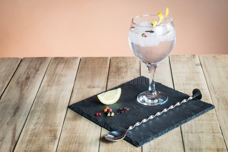 Gin Tonic avec des botanicals et cuillère de barre sur la table en bois image libre de droits