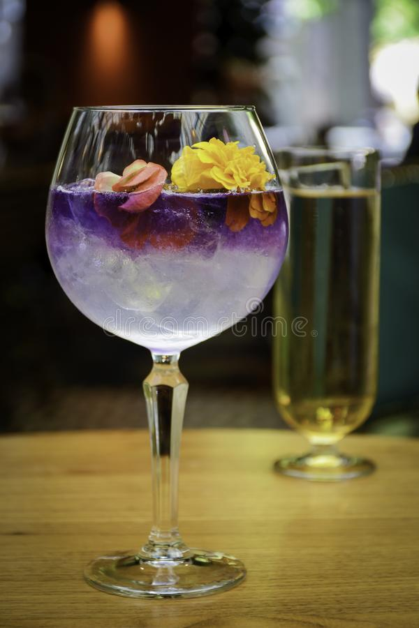 Cocktail glasses. Ice cold modern craft cocktail garnished by some flowers on a table with blurry restaurant background stock image