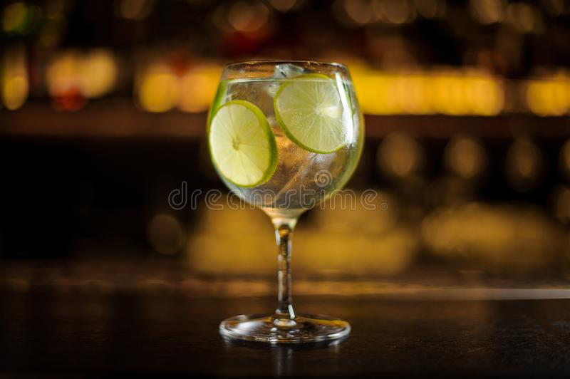 Gin Tonic-cocktail met kalkplakken die wordt verfraaid stock foto's