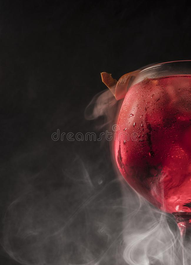 Gin and tonic glass with smoke and dark background stock photo