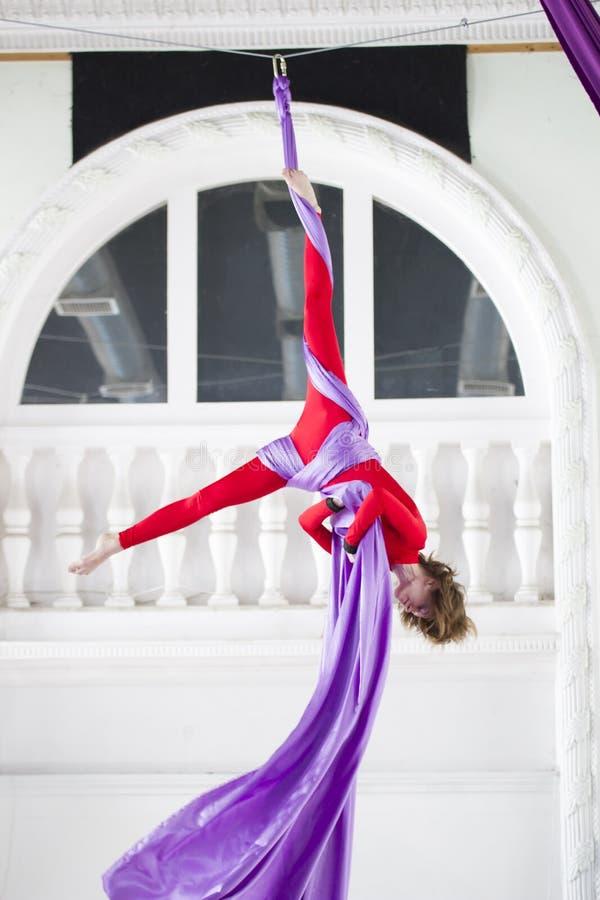 A ginasta atrativa nova do ar executa um exercício que pendura na seda aérea fotos de stock