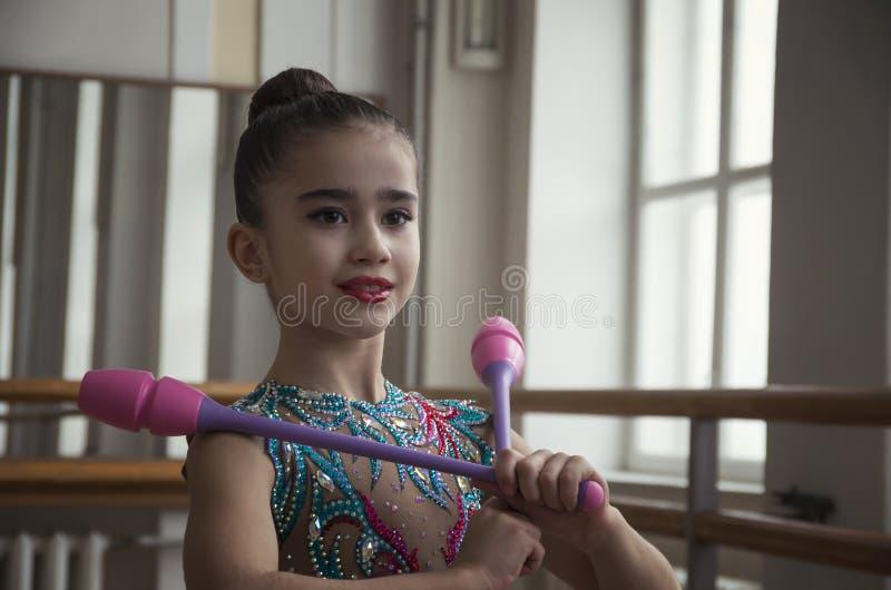 Ginasta da moça com os clubes nas mãos no gym A ginasta da moça com clubes olha através de uma grande janela no salão fotografia de stock