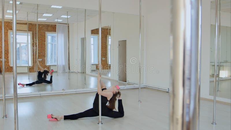 A ginasta flexível mostra-lhe a guita em um pilão em um estúdio fotos de stock royalty free