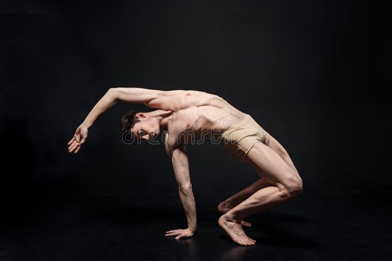A ginasta nova elástica que estica na obscuridade iluminou o estúdio fotos de stock royalty free