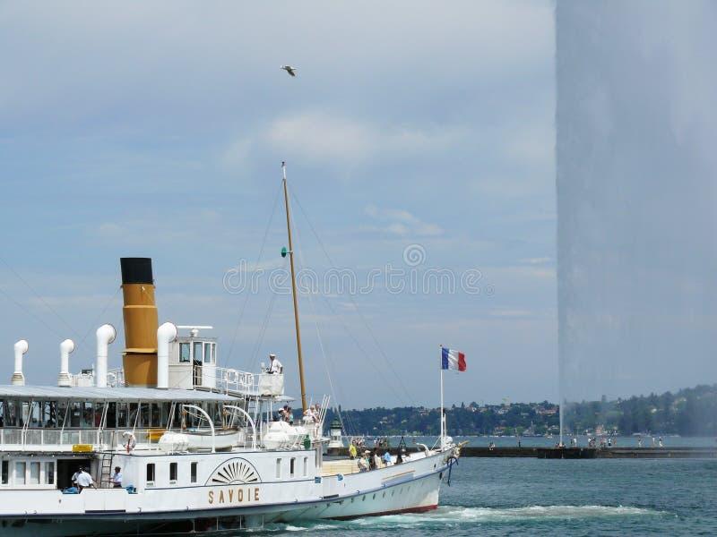 Ginebra, Suiza 07/31/2009 Barco en el lago y el chorro de agua fotos de archivo libres de regalías
