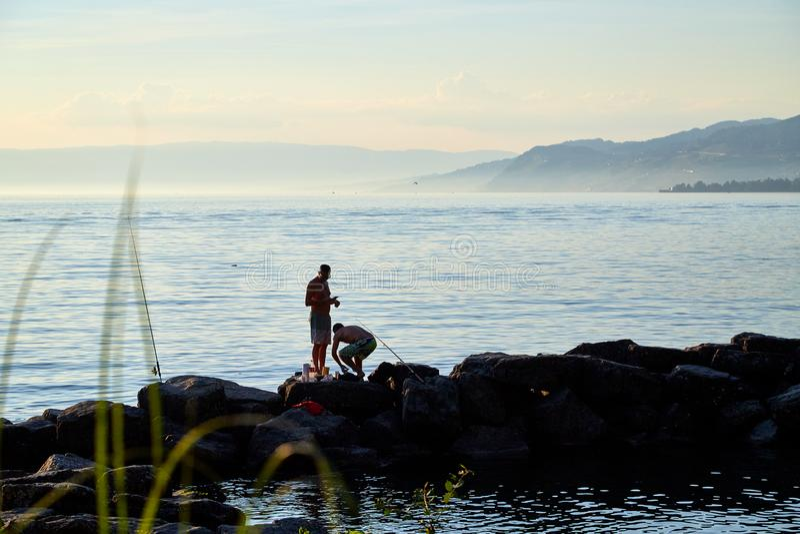 Ginebra, Suiza - 20 de septiembre de 2018: Siluetas de pescadores en el lago en la puesta del sol foto de archivo