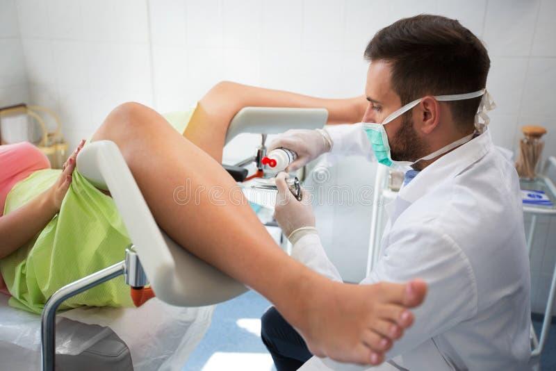 Ginecologista novo que põe o gel sobre o equipamento ao paciente do exame imagem de stock