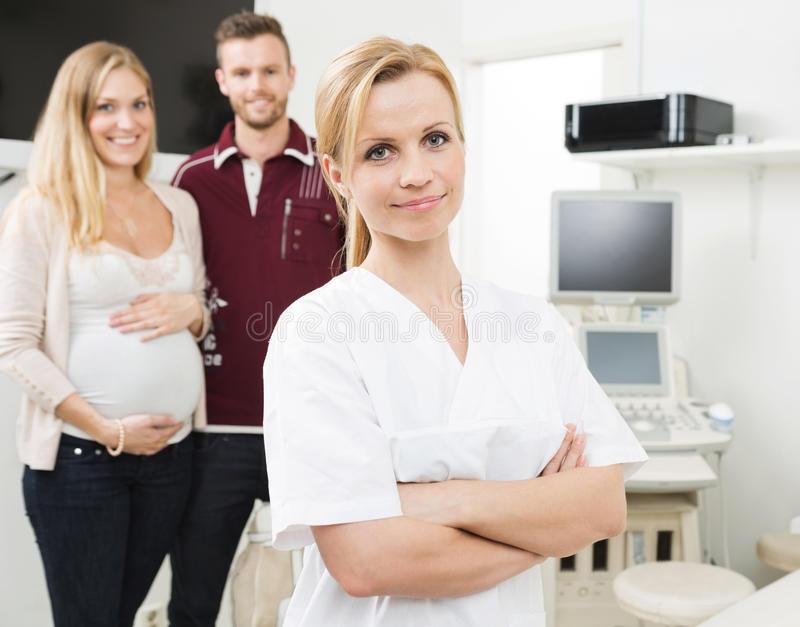 Ginecologo sicuro With Expectant Couple dentro immagini stock