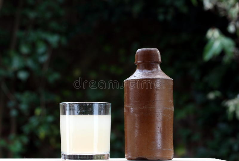 Ginger beer. An old stoneware ginger beer bottle, and glass of ginger beer royalty free stock image