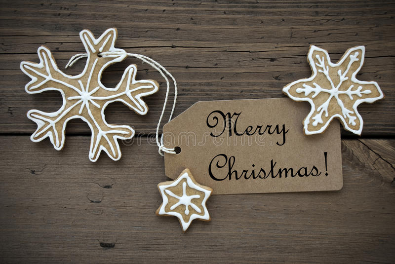 Ginger Bread Stars with Merry Christmas Label. Ginger Bread Stars with white Decoration and a Label on which stands Merry Christmas, on Wooden Background stock photos