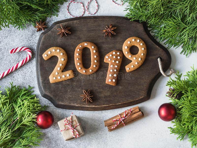 Ginger Christmas or New Year cookies in the form of numbers 2019 on a dark wood board on gray background. top view. Seasonal packa stock photo