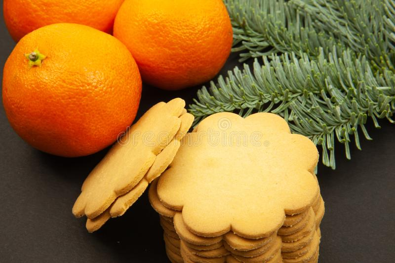 Ginger cookies, fir branches and tangerines, on a dark background, close-up royalty free stock images