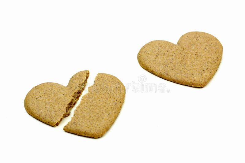 Ginger cookies in the form of a heart on a light background. Cracked heart stock photography