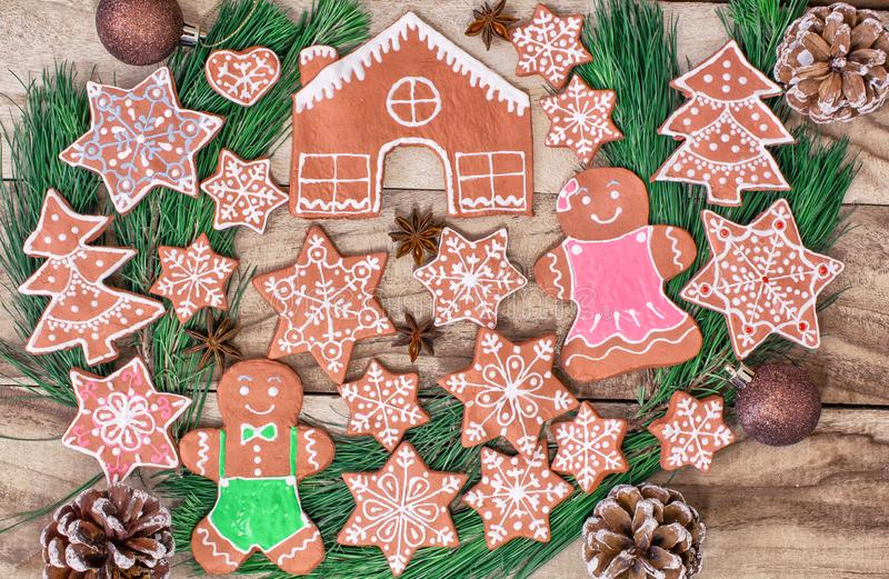 Ginger cookies. Gingerbread house, gingerbread man, stars and fir-tree on wooden background. Festive background royalty free stock photo