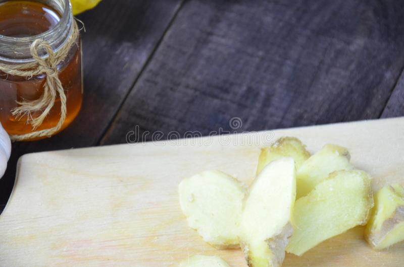 Ginger on cutting board, jar of honey, dried lemon slice, cinnamon and grater on kitchen table. Selective focus. royalty free stock photo