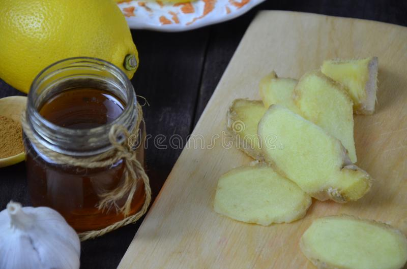 Ginger on cutting board, jar of honey, dried lemon slice, cinnamon and grater on kitchen table. Selective focus. royalty free stock image