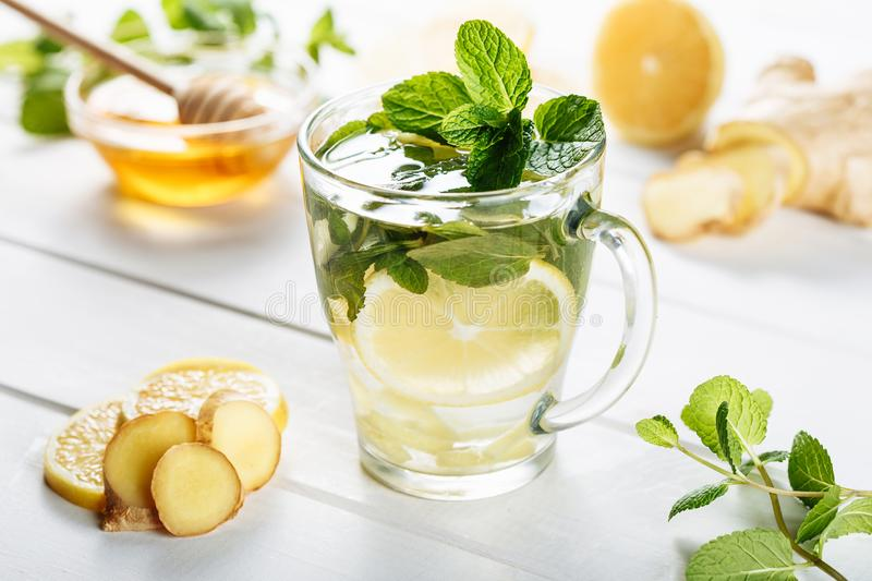 Ginger green tea in a glass for flu cold winter days. Side view on white wooden background decorated with mint, lemon. And honey stock image