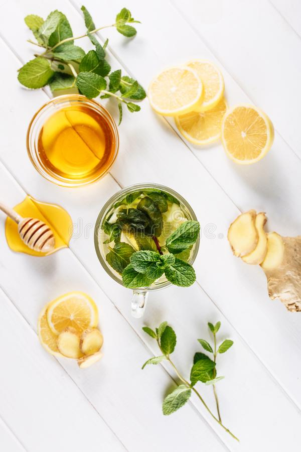 Ginger green tea in a glass for flu cold winter days. Side view on white wooden background decorated with mint, lemon. And honey stock images
