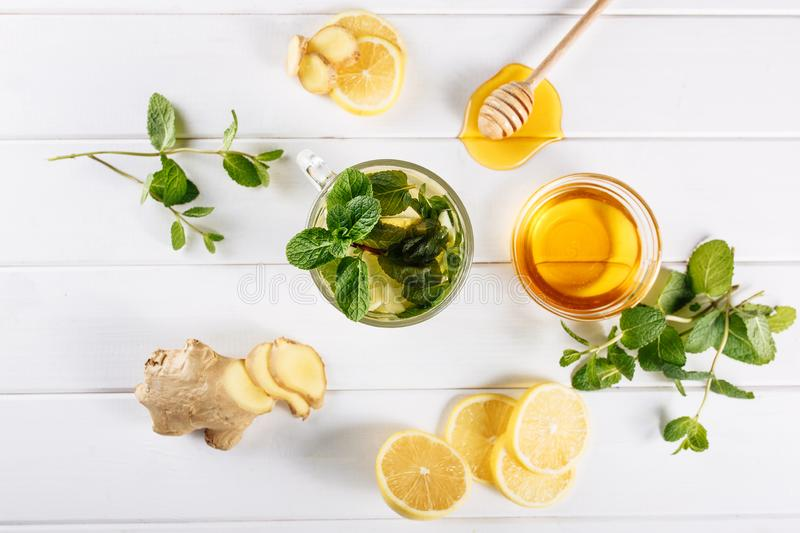 Ginger green tea in a glass for flu cold winter days. Side view on white wooden background decorated with mint, lemon. And honey stock photo