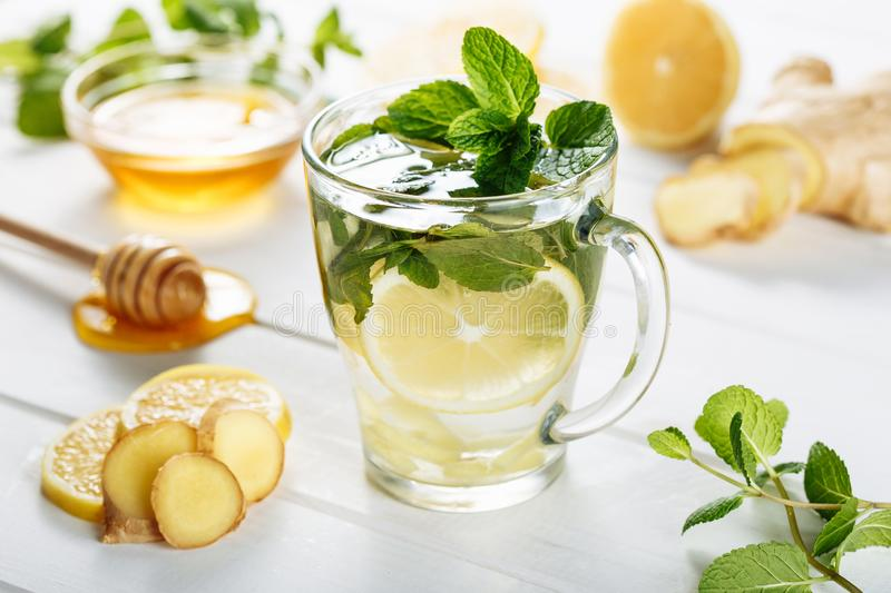 Ginger green tea in a glass for flu cold winter days. Side view on white wooden background decorated with mint, lemon. And honey royalty free stock photography
